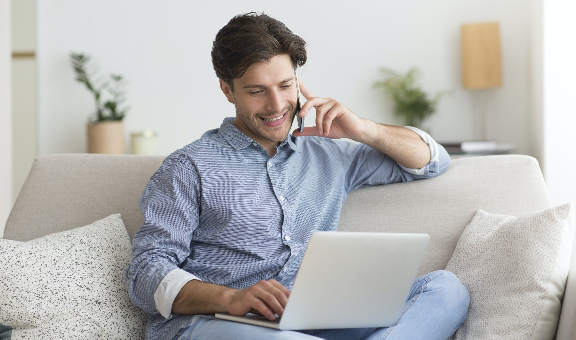 Cheerful Man Talking On Phone Sitting On Sofa Indoor